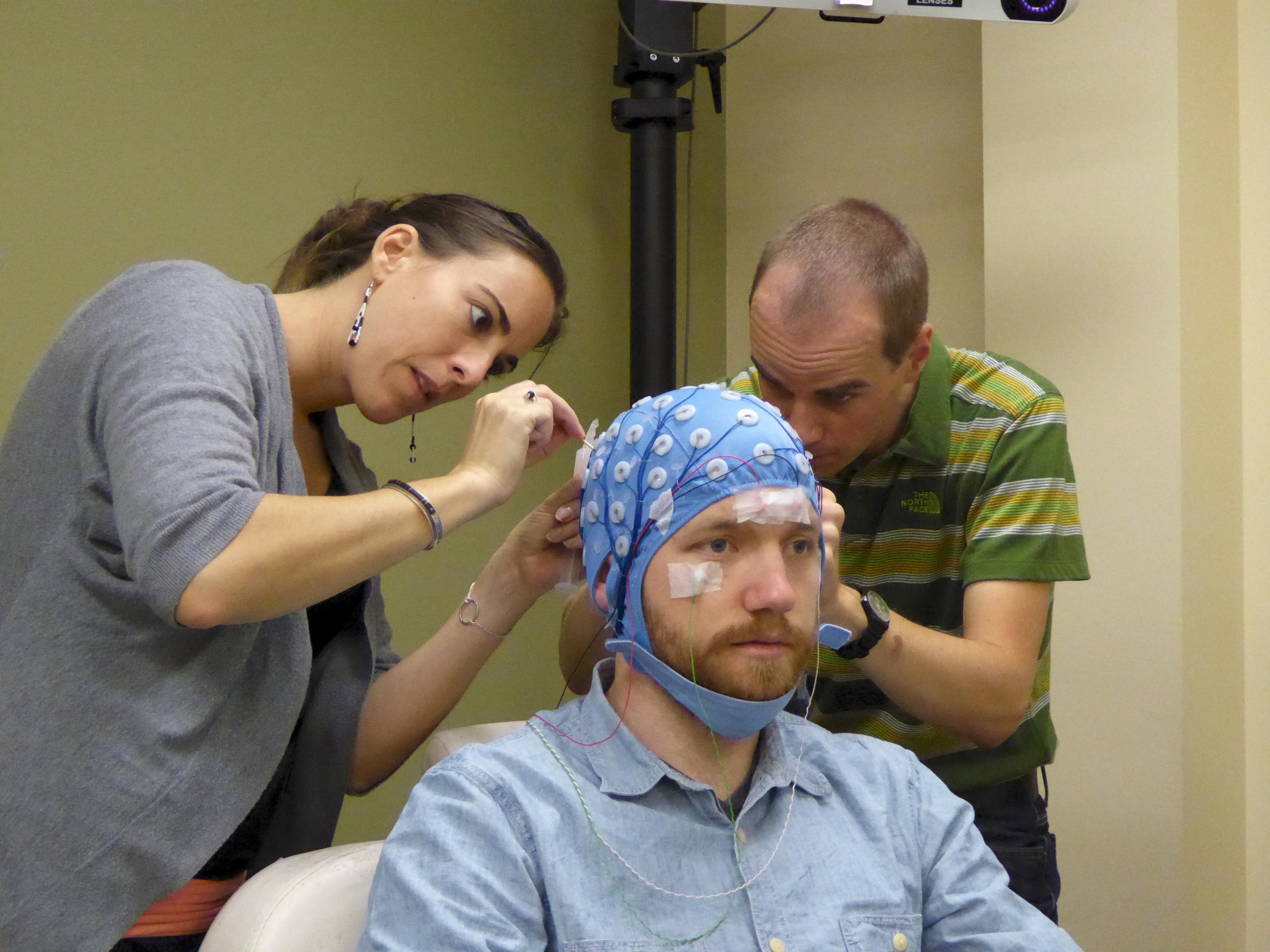 Tutkijat Olivia Gosseries ja Jaakko Nieminen valmistelevat koehenkilöä (Bjørn Erik Juel) mittausta varten. Valokuva: Johan Frederik Storm